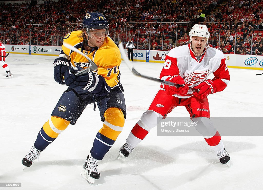 Sergei Kostitsyn #74 of the Nashville Predators battles for the puck with Ian White #18 of the Detroit Red Wings at Joe Louis Arena on February 23, 2013 in Detroit, Michigan. Detroit won the game 4-0.