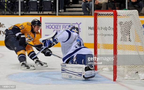 Sergei Kostitsyn of the Nashville Predators puts the puck in the net against goalie Mathieu Garon of the Tampa Bay Lightning during an NHL game on...