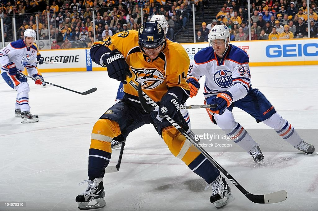 Sergei Kostitsyn #74 of the Nashville Predators ties up the stick of Corey Potter #44 of the Edmonton Oilers at the Bridgestone Arena on March 25, 2013 in Nashville, Tennessee.