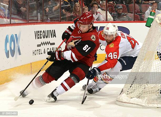 Sergei Plotnikov of the Arizona Coyotes skates the puck around the back of the net while being defended by Jakub Kindl of the Florida Panthers at...