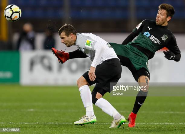 Sergei Sukharev of FC Tosno and Fedor Smolov of FC Krasnodar vie for the ball during the Russian Football League match between FC Tosno and FC...