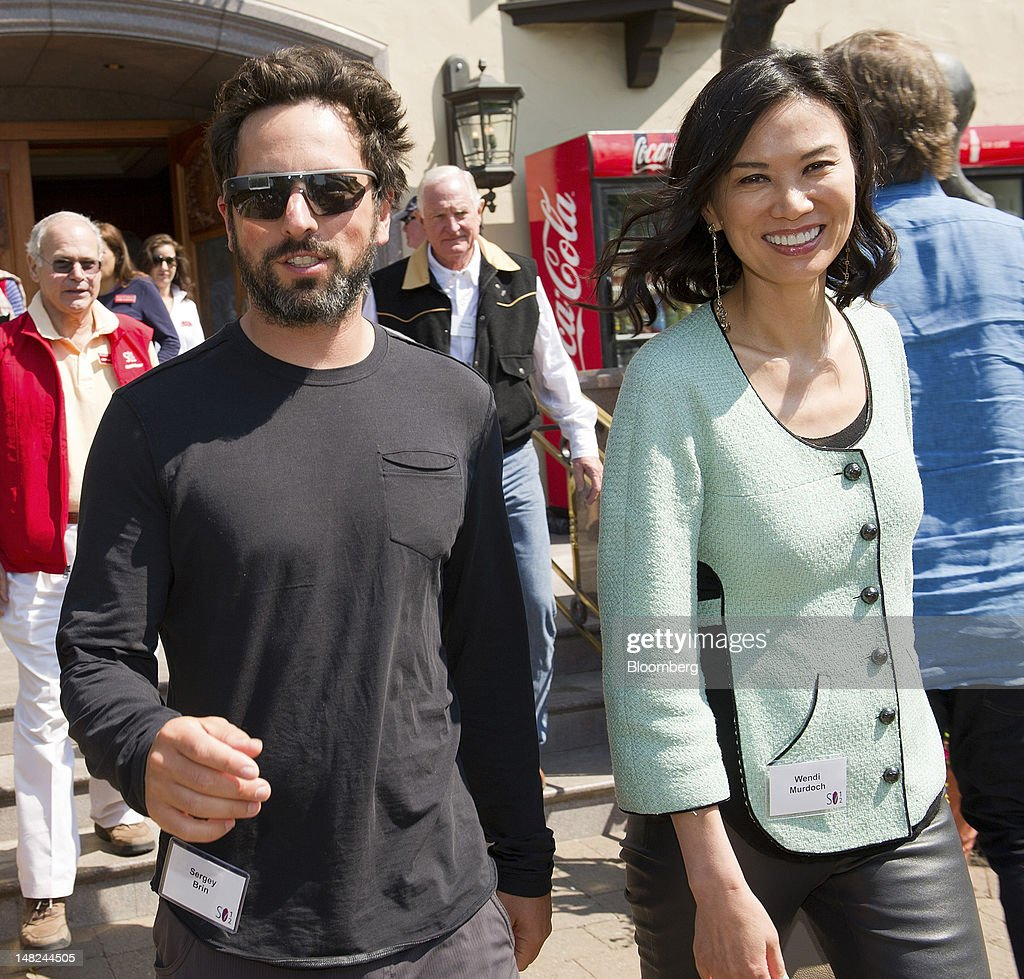 Sergey Brin, co-founder of Google Inc., wearing Project Glass internet glasses, left, and Wendi Deng leave the morning session during the Allen & Co. Media and Technology Conference in Sun Valley, Idaho, U.S., on Thursday, July 12, 2012. Media moguls gathered at the annual Allen & Co. conference have spent recent years contemplating how to cope with technology companies drawing audiences away from television and movies. Photographer: David Paul Morris/Bloomberg via Getty Images