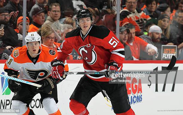 Sergey Kalinin of the New Jersey Devils skates against Travis Konecny of the Philadelphia Flyers on January 21 2017 at the Wells Fargo Center in...