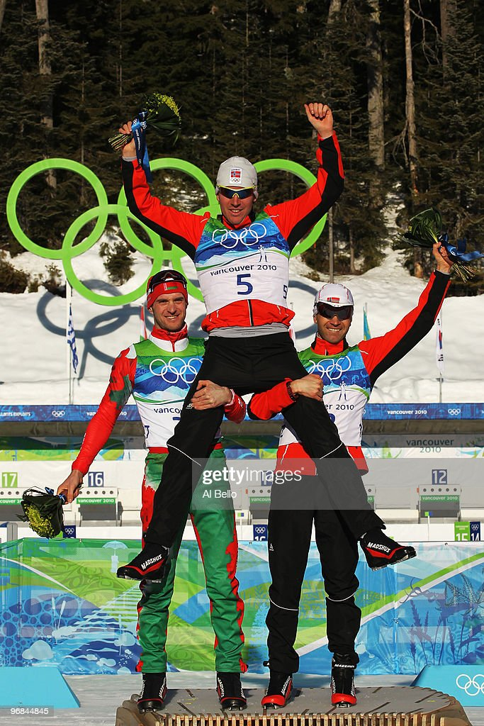 Sergey Novikov of Belarus celebrates winning silver, <a gi-track='captionPersonalityLinkClicked' href=/galleries/search?phrase=Emil+Hegle+Svendsen&family=editorial&specificpeople=831528 ng-click='$event.stopPropagation()'>Emil Hegle Svendsen</a> of Norway gold and <a gi-track='captionPersonalityLinkClicked' href=/galleries/search?phrase=Ole+Einar+Bjoerndalen&family=editorial&specificpeople=206663 ng-click='$event.stopPropagation()'>Ole Einar Bjoerndalen</a> of Belarus silver during the flower ceremony for the Biathlon Men's 120 km individual on day 7 of the 2010 Vancouver Winter Olympics at Whistler Olympic Park Biathlon Stadium on February 18, 2010 in Whistler, Canada