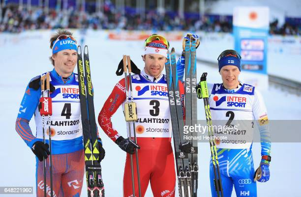 Sergey Ustiugov of Russia Alex Harvey of Canada and Matti Heikkinen of Finland pose for the media after in the Men's Cross Country Mass Start during...
