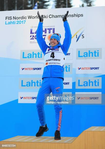 Sergey Ustiugov of Russia celebrates winning the silver medal in the Men's Cross Country Mass Start during the flower ceromeny during the FIS Nordic...