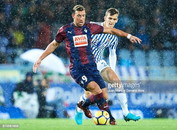 Sergi Enrich of SD Eibar being followed by Diego Llorente of Real Sociedad during the La Liga match between Real Sociedad and Eibar at Estadio Anoeta...