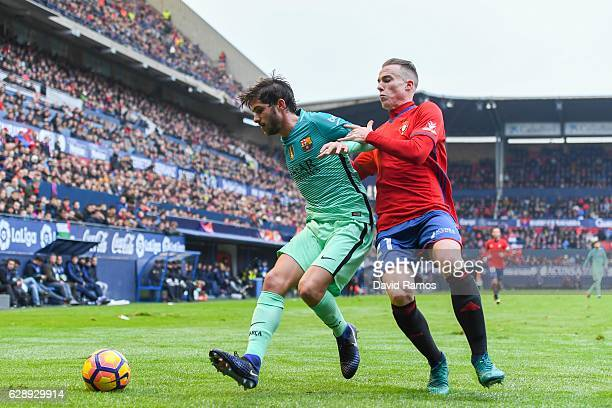 Sergi Roberto of FC Barcelona competes for the ball with Javier Flano of CA Osasuna during the La Liga match between CA Osasuna and FC Barcelona at...