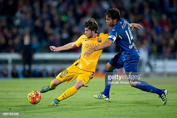 Sergi Roberto of FC Barcelona competes for the ball with Pedro Leon of Getafe CF during the La Liga match between Getafe CF and FC Barcelona at...
