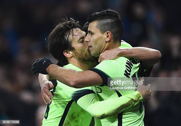 Sergio Aguero and David Silva of Manchester City congratulate goalscorer Jesus Navas during the Capital One Cup Semi Final First Leg match between...