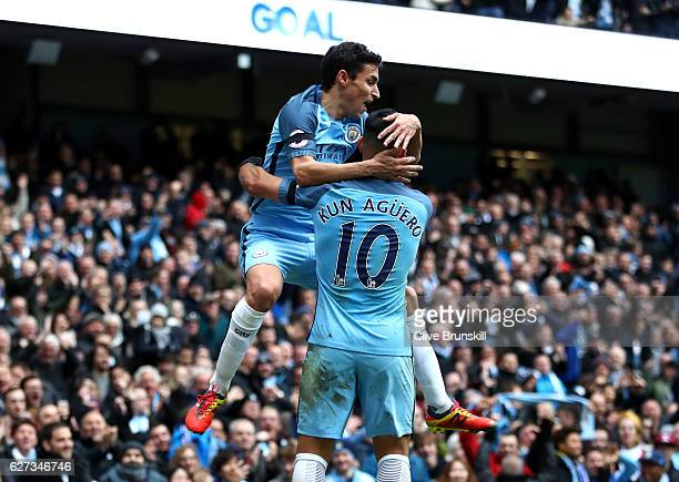 Sergio Aguero and Jesus Navas of Manchester City celebrate their team's first goal during the Premier League match between Manchester City and...
