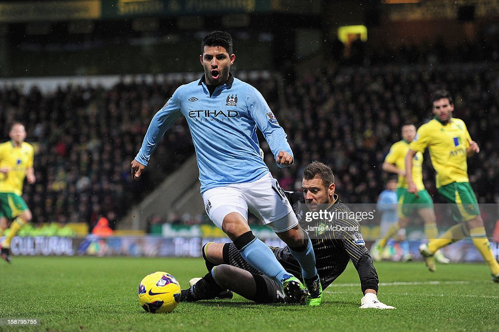 Sergio Aguero of Manchester City and Mark Bunn of Norwich City battle for the ball during the Barclays Premier League match between Norwich City and Manchester City at Carrow Road on December 29, 2012 in Norwich, England.