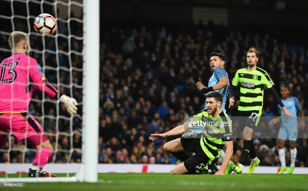 Sergio Aguero of Manchester City beats Mark Hudson and goalkeeper Joel Coleman of Huddersfield Town as he scores their fourth goal during The Emirates FA Cup Fifth Round Replay match between Manchester City and Huddersfield Town at Etihad Stadium on March 1, 2017 in Manchester, England.