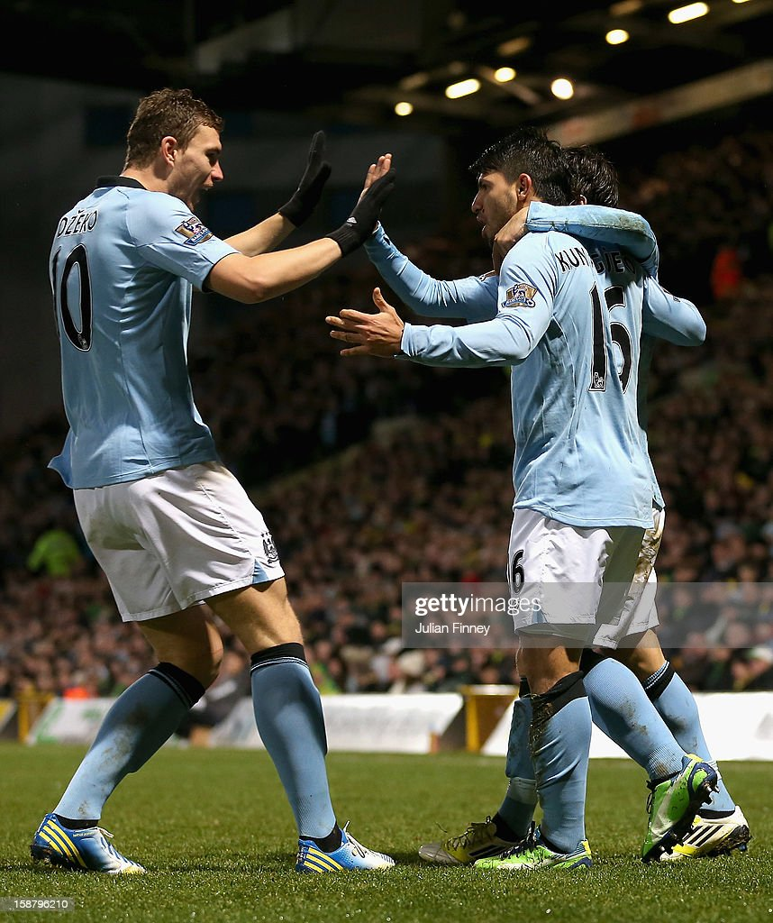 Sergio Aguero of Manchester City celebrates scoring his side's third goal with team mate Edin Dzeko (L) during the Barclays Premier League match between Norwich City and Manchester City at Carrow Road on December 29, 2012 in Norwich, England.