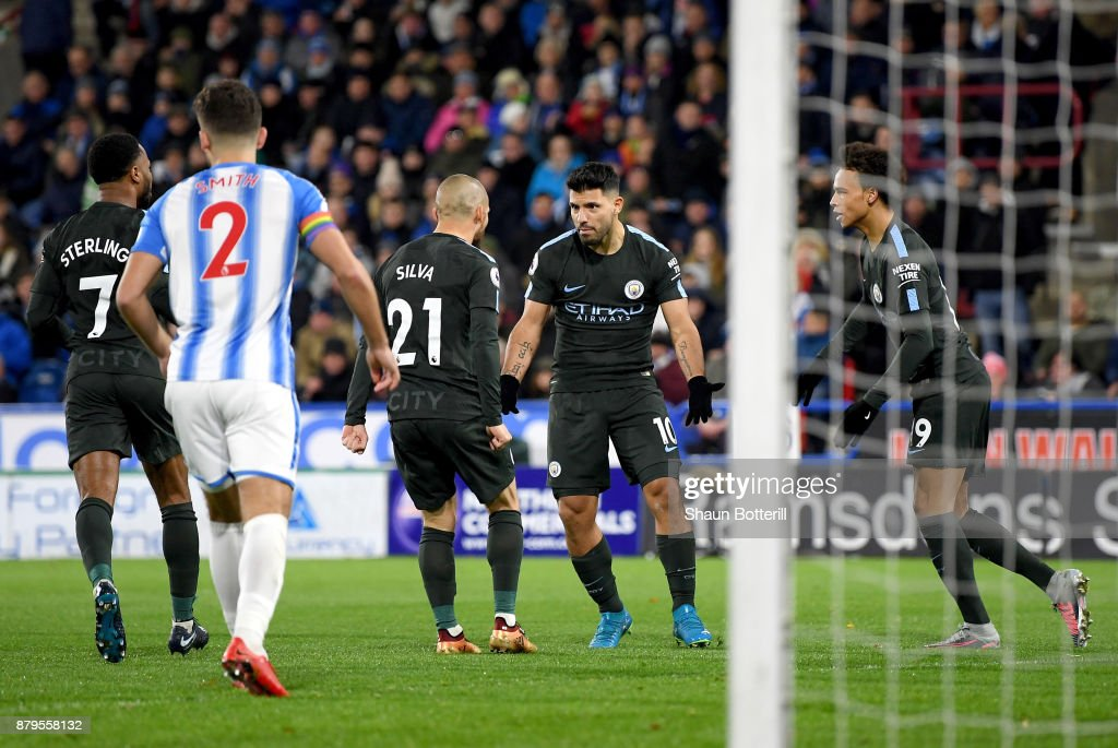 Sergio Aguero of Manchester City celebrates scoring the first Manchester City goal with David Silva, Leroy Sane and Raheem Sterling during the Premier League match between Huddersfield Town and Manchester City at John Smith's Stadium on November 26, 2017 in Huddersfield, England.