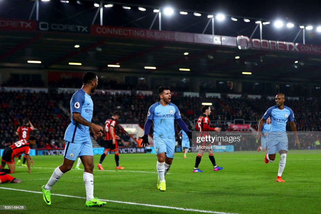 Sergio Aguero of Manchester City celebrates with Raheem Sterling and Fernandinho after sliding in next to Tyrone Mings of Bournemouth to score his team's second goal during the Premier League match between AFC Bournemouth and Manchester City at Vitality Stadium on February 13, 2017 in Bournemouth, England.