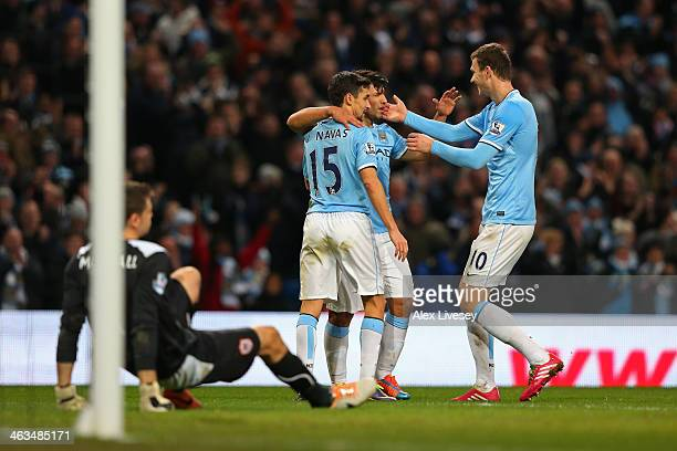 Sergio Aguero of Manchester City celebrates with teammates Jesus Navas and Edin Dzeko after scoring his team's fourth goal during the Barclays...