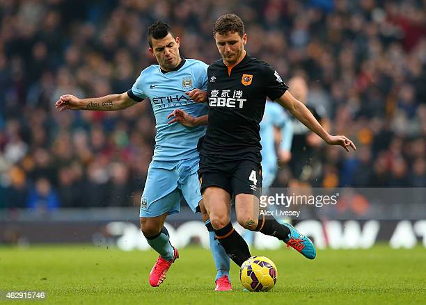 Sergio Aguero of Manchester City competes with Alex Bruce of Hull City during the Barclays Premier League match between Manchester City and Hull City...