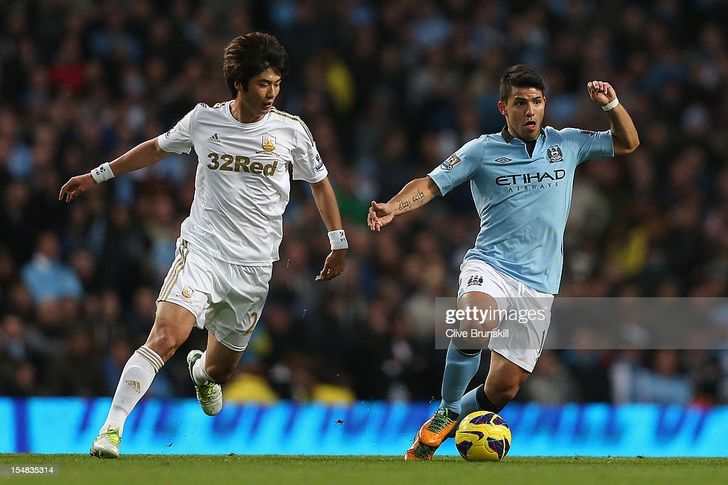 Sergio Aguero of Manchester City competes with Ki Sung- Yeung of Swansea City during the Barclays Premier League match between Manchester City and Swansea City at the Etihad Stadium on October 27, 2012 in Manchester, England.
