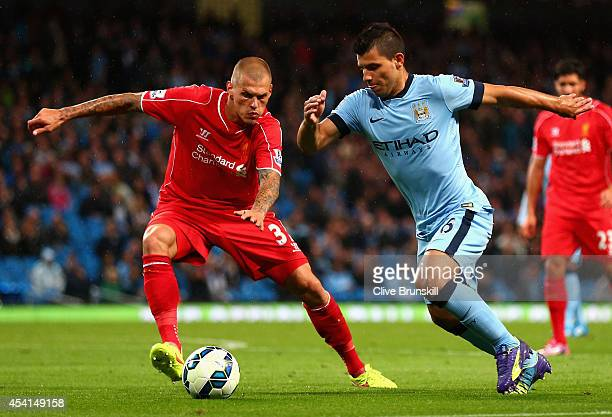 Sergio Aguero of Manchester City competes with Martin Skrtel of Liverpool during the Barclays Premier League match between Manchester City and...
