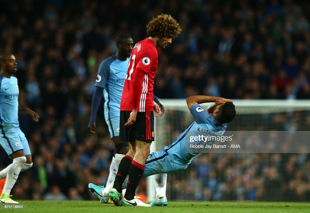 Sergio Aguero of Manchester City falls to the ground after clashing heads with Marouane Fellaini of Manchester United during the Premier League match between Manchester City and Manchester United at Etihad Stadium on April 27, 2017 in Manchester, England.