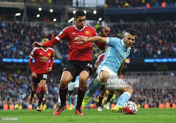 Sergio Aguero of Manchester City holds off Chris Smalling of Manchester United during the Barclays Premier League match between Manchester City and...
