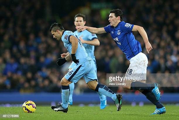 Sergio Aguero of Manchester City is challenged by Gareth Barry of Everton during the Barclays Premier League match between Everton and Manchester...