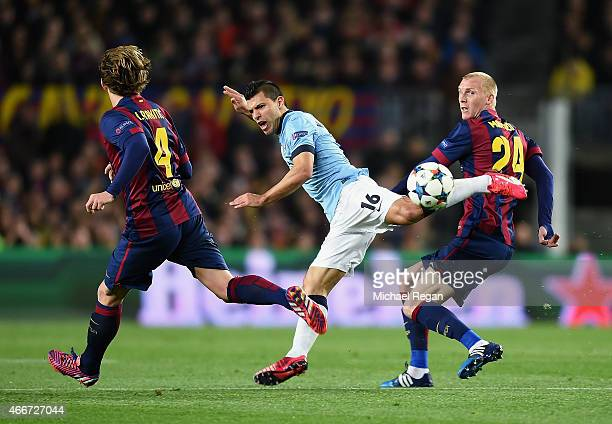Sergio Aguero of Manchester City is challenged by Jeremy Mathieu and Ivan Rakitic of Barcelona during the UEFA Champions League Round of 16 second...