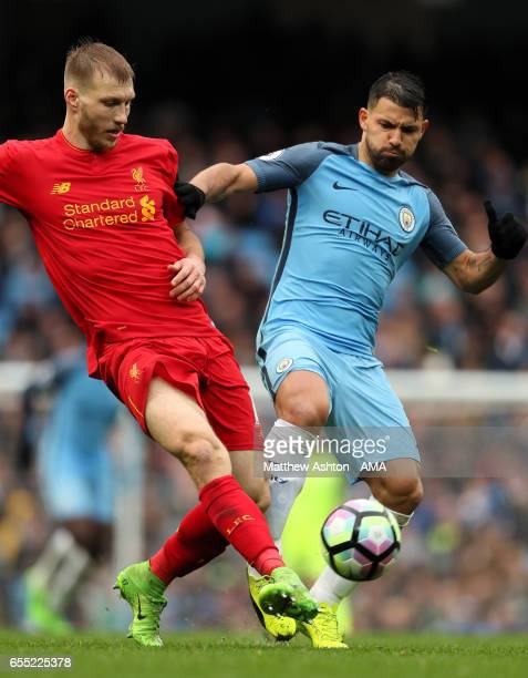Sergio Aguero of Manchester City is challenged by Ragnar Klavan of Liverpool during the Premier League match between Manchester City and Liverpool at...
