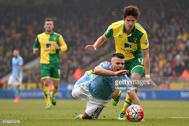 Sergio Aguero of Manchester City is challenged by Timm Klose of Norwich City during the Barclays Premier League match between Norwich City and...