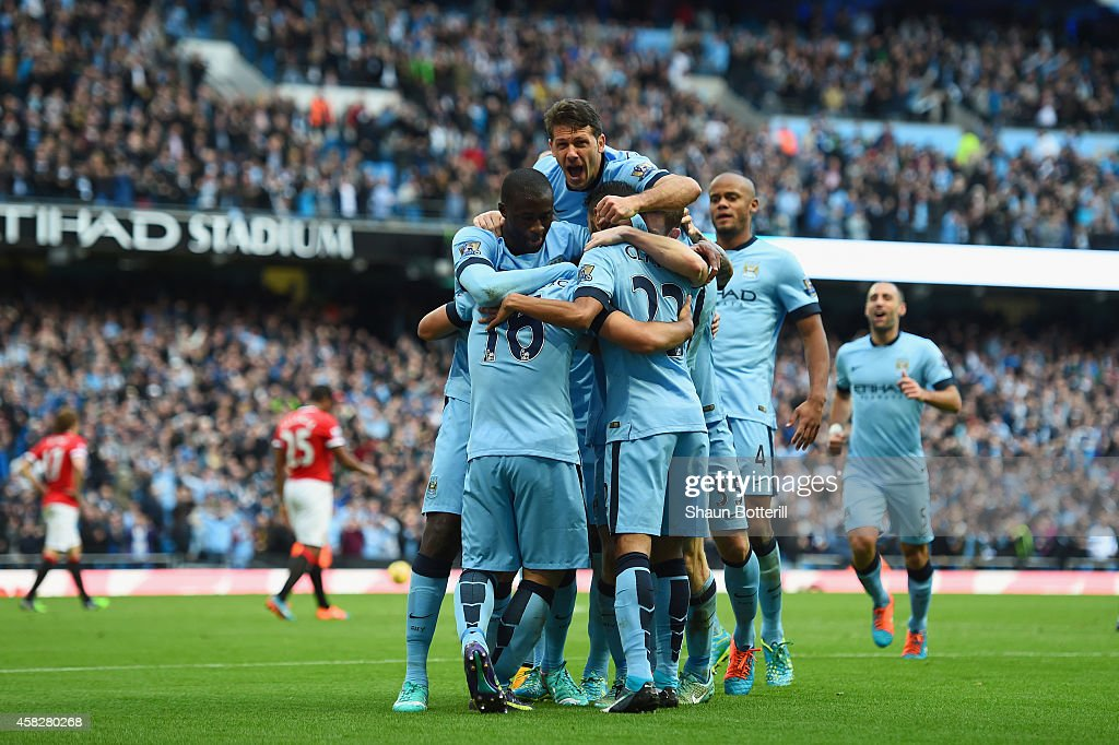 Sergio Aguero of Manchester City is mobbed by team mates after scoring the opening goal during the Barclays Premier League match between Manchester City and Manchester United at Etihad Stadium on November 2, 2014 in Manchester, England.