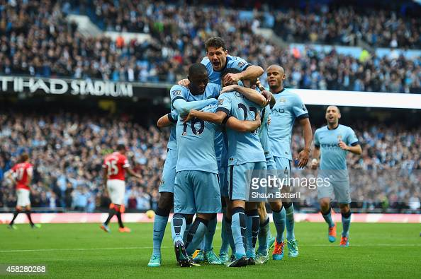 Sergio Aguero of Manchester City is mobbed by team mates after scoring the opening goal during the Barclays Premier League match between Manchester...