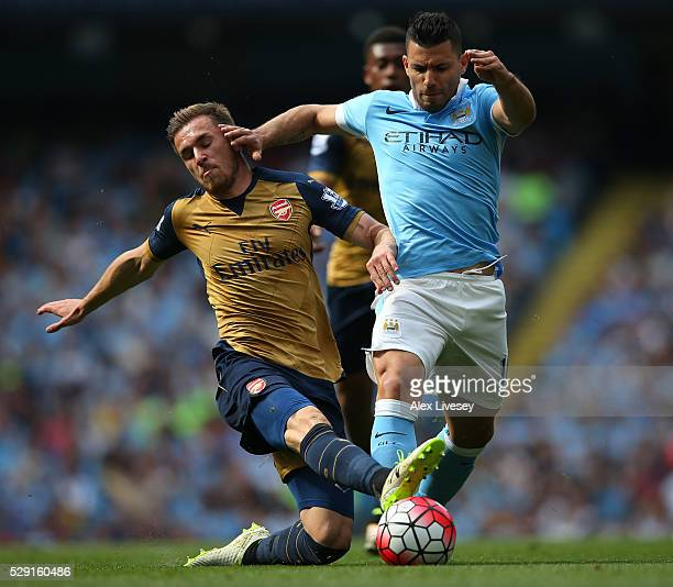 Sergio Aguero of Manchester City is tackled Aaron Ramsey of Arsenal during the Barclays Premier League match between Manchester City and Arsenal at...