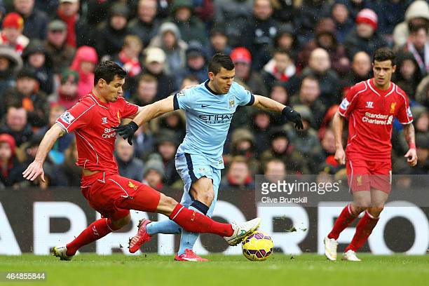 Sergio Aguero of Manchester City is tackled by Dejan Lovren of Liverpool during the Barclays Premier League match between Liverpool and Manchester...