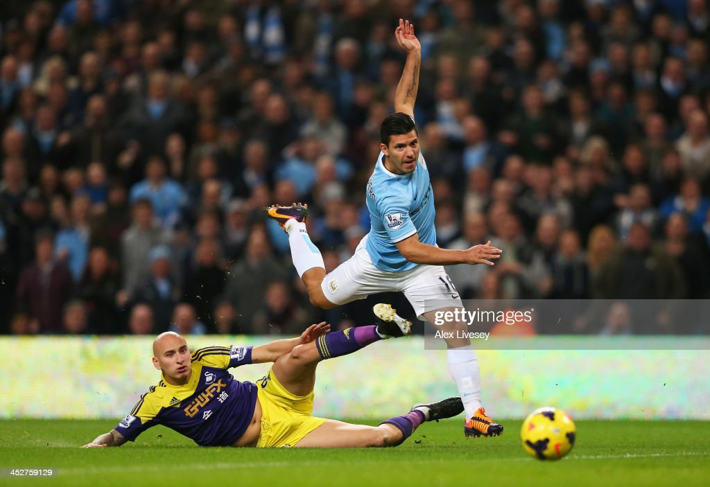 <a gi-track='captionPersonalityLinkClicked' href=/galleries/search?phrase=Sergio+Aguero&family=editorial&specificpeople=1100704 ng-click='$event.stopPropagation()'>Sergio Aguero</a> of Manchester City is tackled by <a gi-track='captionPersonalityLinkClicked' href=/galleries/search?phrase=Jonjo+Shelvey&family=editorial&specificpeople=4940315 ng-click='$event.stopPropagation()'>Jonjo Shelvey</a> of Swansea City as he shoots at goal during the Barclays Premier League match between Manchester City and Swansea City at Etihad Stadium on December 1, 2013 in Manchester, England.