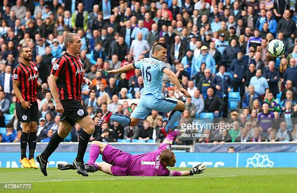 Sergio Aguero of Manchester City lifts the ball over the diving Robert Green of QPR to score the opening goal during the Barclays Premier League...