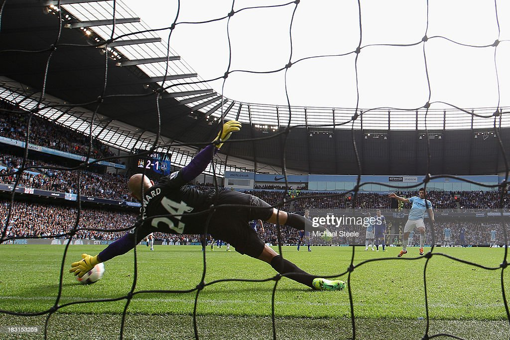 Sergio Aguero (R) of Manchester City scores from a penalty as goalkeeperTim Howard of Everton dives in vain during the Barclays Premier League match between Manchester City and Everton at the Etihad Stadium on October 5, 2013 in Manchester, England.