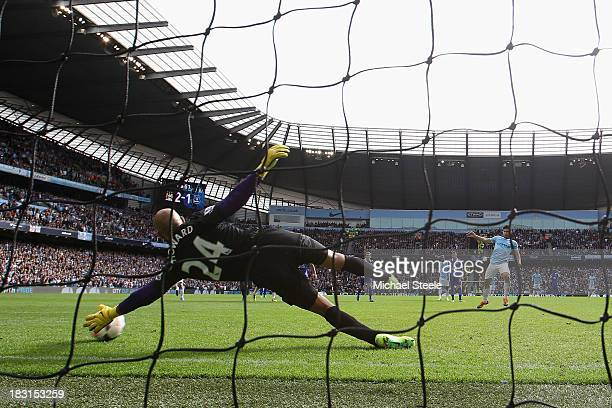 Sergio Aguero of Manchester City scores from a penalty as goalkeeperTim Howard of Everton dives in vain during the Barclays Premier League match...