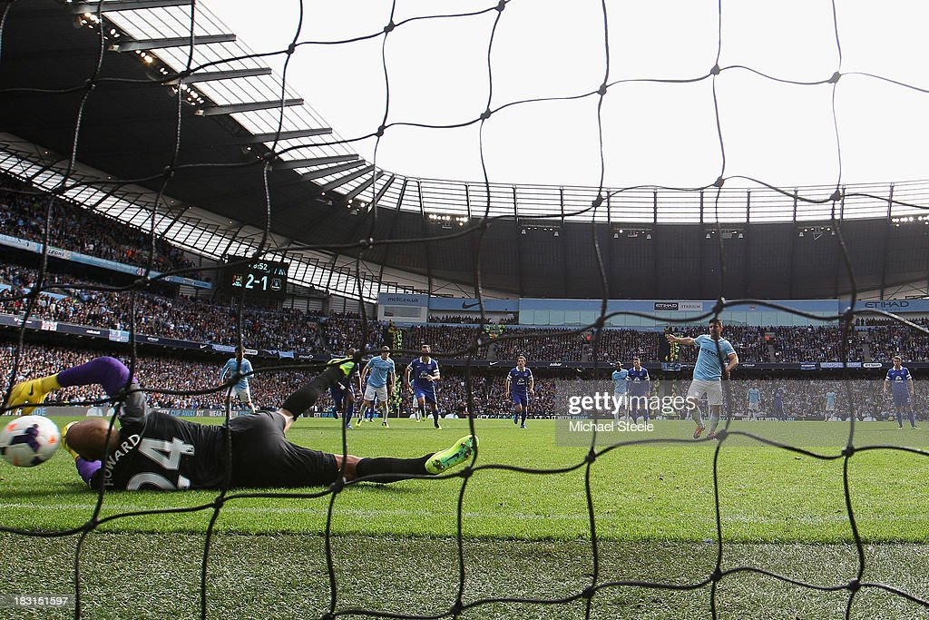 Sergio Aguero (R) of Manchester City scores from a penalty as the ball rebounds off the post and hits goalkeeperTim Howard of Everton during the Barclays Premier League match between Manchester City and Everton at the Etihad Stadium on October 5, 2013 in Manchester, England.