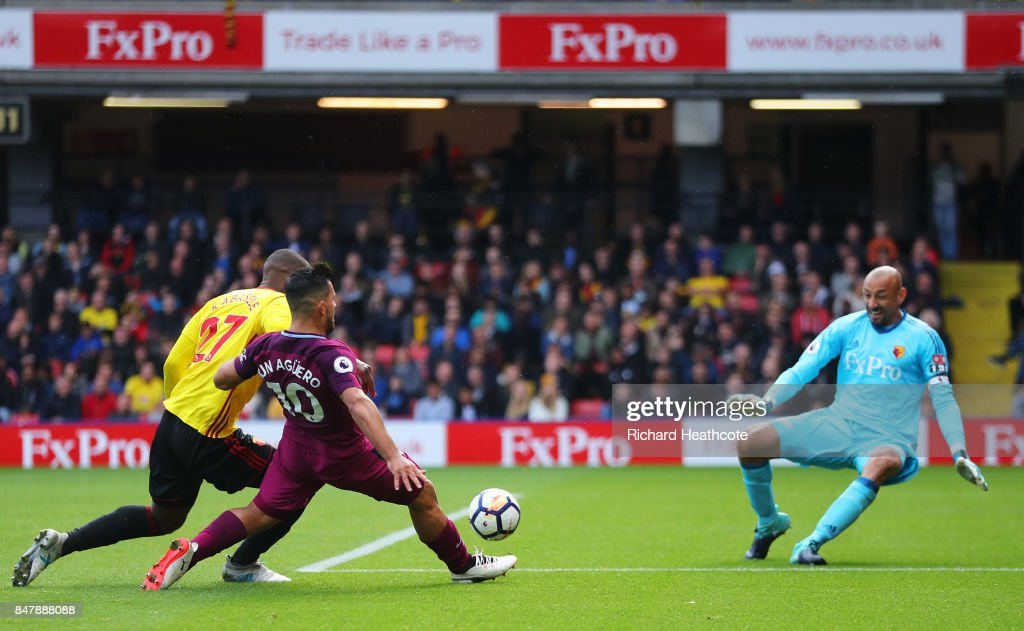 Sergio Aguero of Manchester City scores his sides fifth goal past Heurelho Gomes of Watford while under pressure from Christian Kabasele of Watford during the Premier League match between Watford and Manchester City at Vicarage Road on September 16, 2017 in Watford, England.