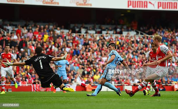 Sergio Aguero of Manchester City scores the opening goal past Wojciech Szczesny of Arsenal during the Barclays Premier League match between Arsenal...