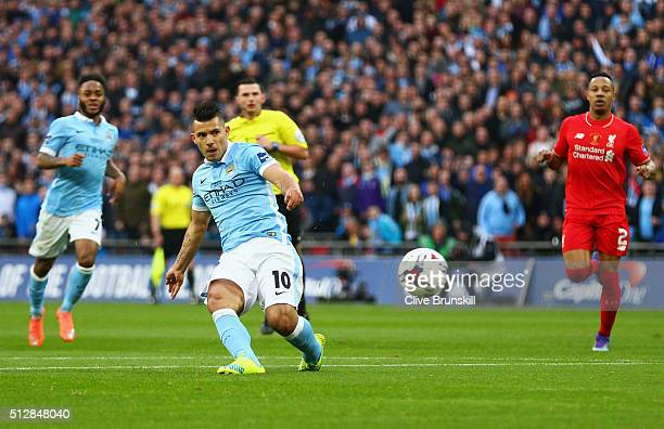 Sergio Aguero of Manchester City shoots as goal but is foiled by goalkeeper Simon Mignolet of Liverpool and the post during the Capital One Cup Final...