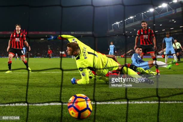 Sergio Aguero of Manchester City slides in next to Tyrone Mings of Bournemouth to score his team's second goal past Artur Boruc of Bournemouth during...