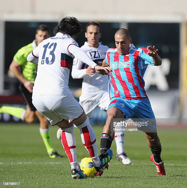 Sergio Almiron of Catania competes for the ball with Kakha Kaladze of Genoa during the Serie A match between Catania Calcio and Genoa CFC at Stadio...