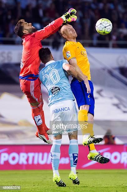 Sergio Alvarez of Celta Vigo clears the ball next to his teammate Sergi Gomez and Jeremy Mathieu of FC Barcelona during the La Liga match between...