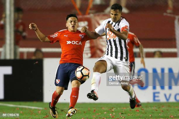 Sergio Aquino of Libertad fights for the ball with Ezequiel Barco of Independiente during a second leg match between Independiente and Libertad as...