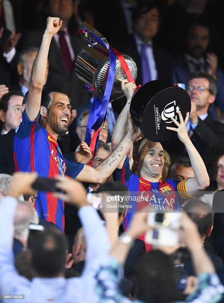 Sergio Busquets (L) and Andres Iniesta of FC Barcelona hold up the trophy after winning the Copa Del Rey Final between FC Barcelona and Deportivo Alaves at Vicente Calderon stadium on May 27, 2017 in Madrid, Spain.
