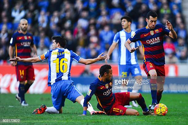 Sergio Busquets and Neymar of FC Barcelona competes for the ball with Javi Lopez of RCD Espanyol during the La Liga match between RCD Espanyol and FC...