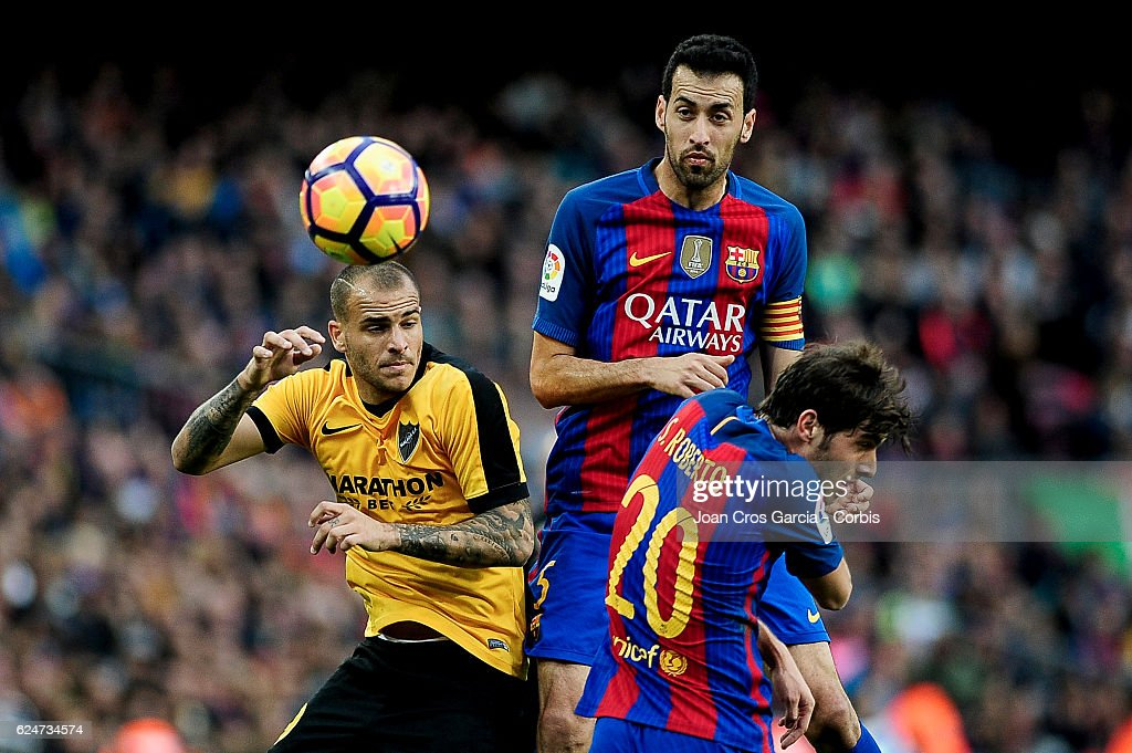Sergio Busquets and Sergi Roberto of FC Barcelona compete for the ball with Sandro Ramírez (L) of Malaga CF, during the Spanish League match between FC Barcelona vs Malaga C.F. at Camp Nou Stadium, on November 19, 2016 in Barcelona, Spain.