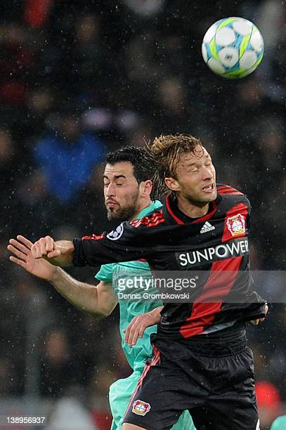 Sergio Busquets of Barcelona and Simon Rolfes of Leverkusen jump for a header during the UEFA Champions League round of sixteen first leg match...